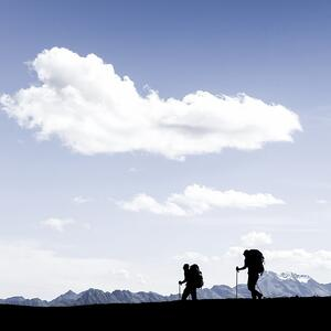 silhouettes-of-two-hikers-walking-along-the-cliff-edge-picture-id1136240420